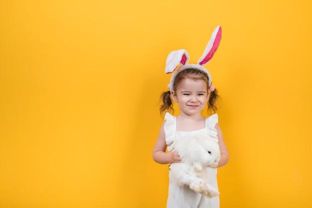 Милая девушка в ушах зайчика стоя с кроликом Бесплатные Фотографии
