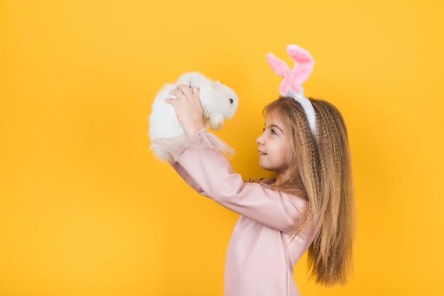 Милая девушка в ушах зайчика смотря кролика Бесплатные Фотографии