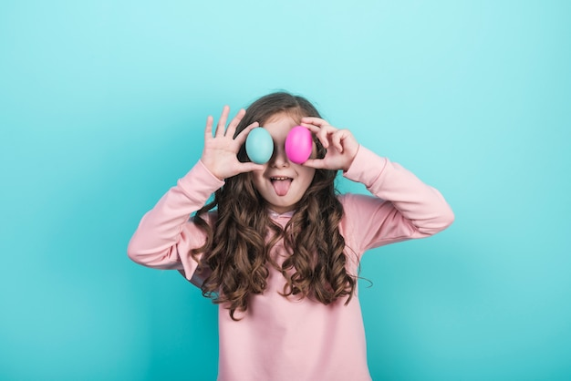 目にイースターエッグを保持している小さな女の子 無料写真
