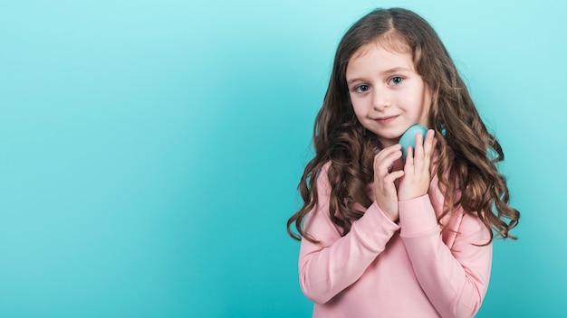 青いイースターエッグを保持しているかわいい女の子 無料写真