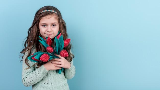 Маленькая девочка стоит с игрушечными цветами Бесплатные Фотографии