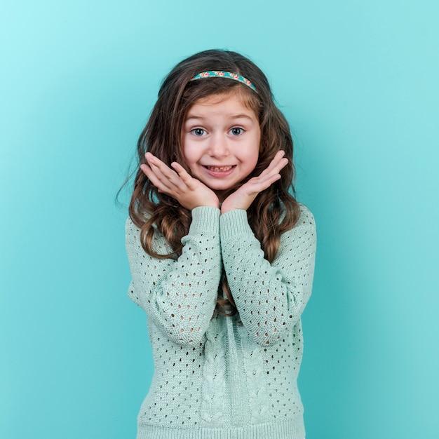 青色の背景に立っている驚きの少女 無料写真