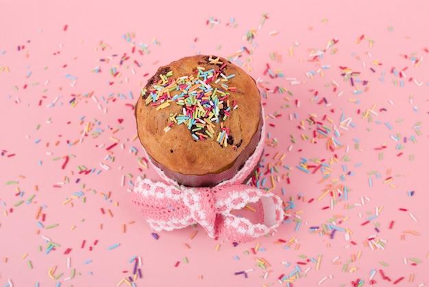 ピンクのテーブルの上の明るい振りかけるとイースターケーキ 無料写真