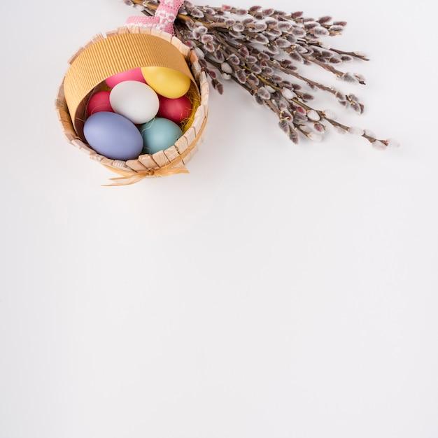 柳の枝を持つ木製のバスケットのイースターエッグ 無料写真