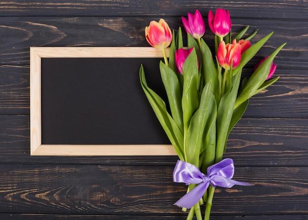 チューリップの花束を持つフレーム黒板 無料写真
