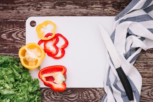 木製の机の上のナイフとナプキンの白いまな板にレタスとピーマン 無料写真