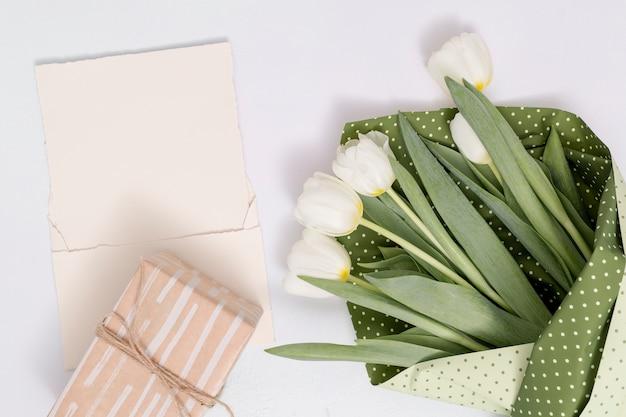 白いチューリップの花の花束のハイアングル。白い背景の上の空白の紙とギフトボックス 無料写真