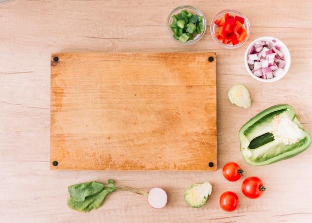 Ломтики красного цвета; зеленый перец; лук; корень свеклы; помидоры черри возле пустой разделочной доски над деревянным столом Бесплатные Фотографии