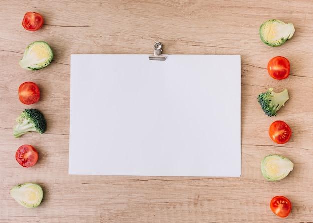 チェリートマトの列。芽キャベツとブロッコリーペーパークリップで空白のホワイトペーパーの近く 無料写真