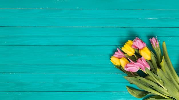 黄色の平面図。緑の木製の机の上のピンクのチューリップの花 無料写真