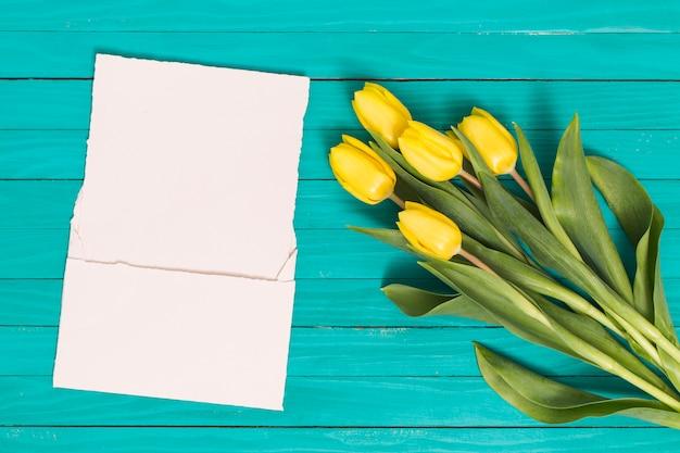緑の机の上の白い空白の紙と黄色のチューリップの花の高角度のビュー 無料写真