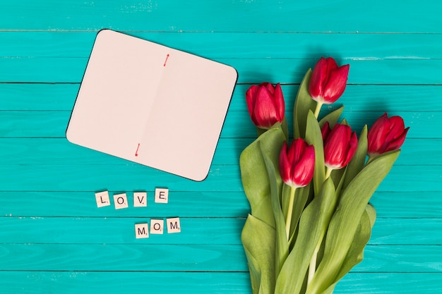 愛の平面図ママのテキスト。空白のカードと緑の木の板の上の赤いチューリップの花 無料写真