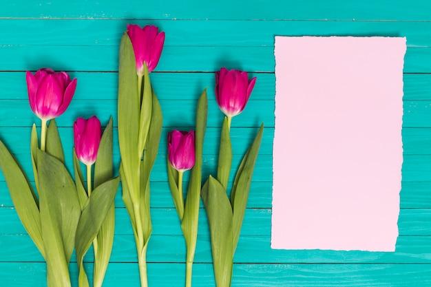 緑の木製の背景に空白の紙とピンクのチューリップの花の立面図 無料写真