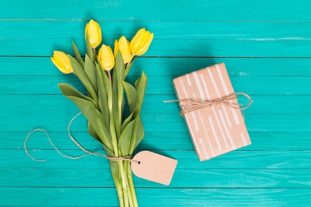 春のチューリップの花。と木製のテーブルの上のギフトボックス 無料写真