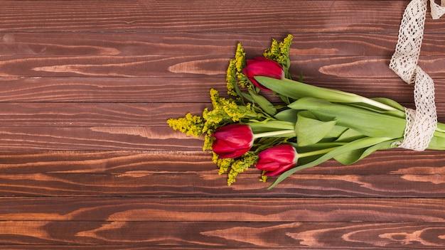 Букет из красных тюльпанов и золотарника, перевязанный кружевом на деревянном фоне Бесплатные Фотографии