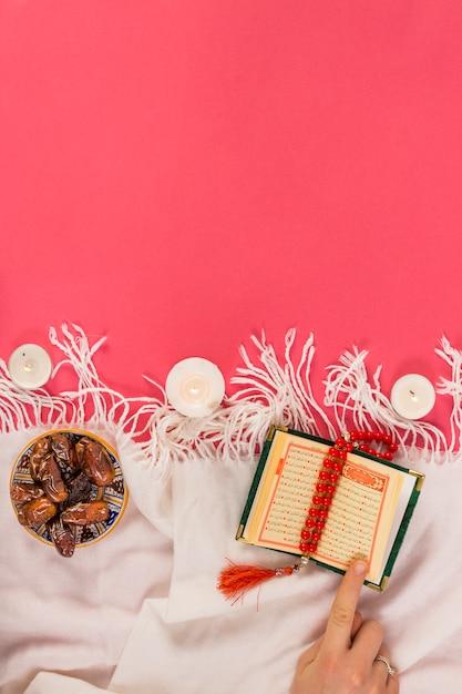 赤いロザリオ。照明キャンドル。コーランと赤の背景上のショールにボウルに日付の聖典 無料写真