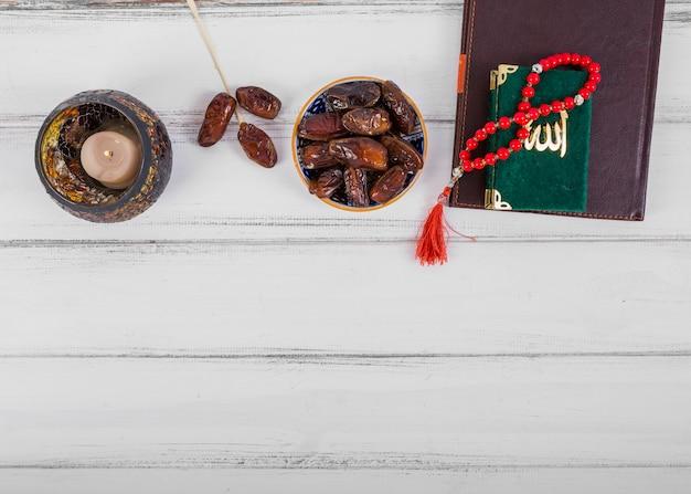 ジューシードライデートボウル。キャンドル;日記;白い木製の机の上のクランとイスラムのロザリオ祈りビーズ 無料写真