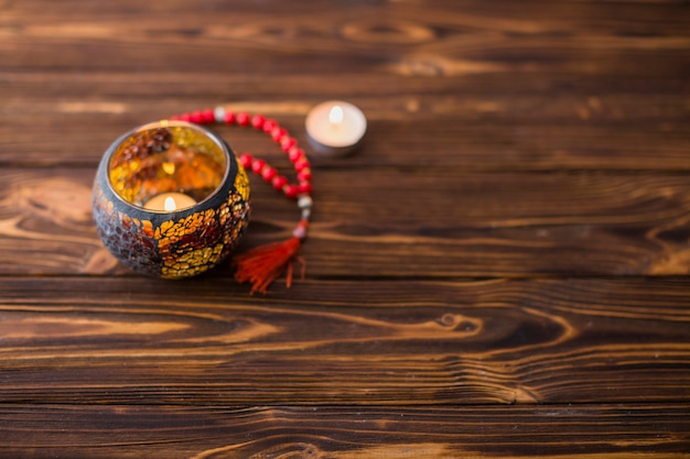 木製の机の上の赤い神聖なビーズとホルダーの中の美しい燃えるろうそく 無料写真
