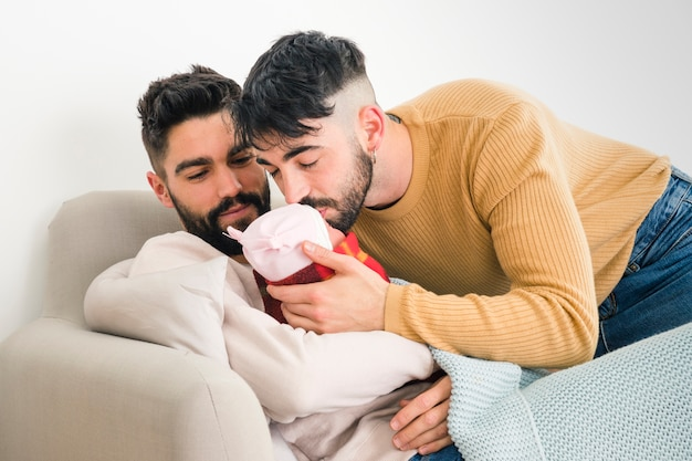 Человек смотрит на своего парня, целуя их спящего ребенка Бесплатные Фотографии