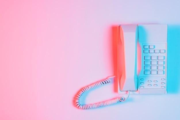 ピンクの背景の上のピンクの固定電話に青い光の焦点 無料写真