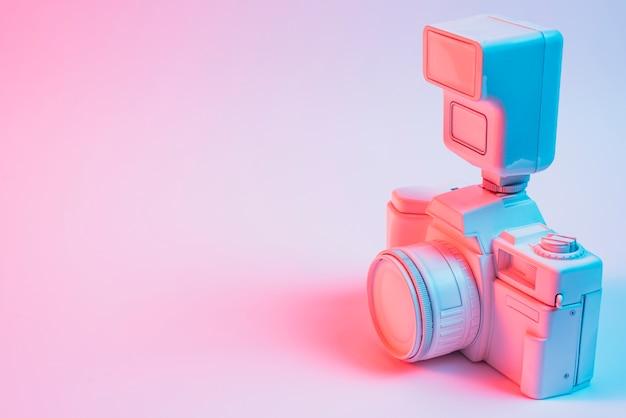 ピンクの背景上のレンズとレトロなビンテージカメラのクローズアップ 無料写真