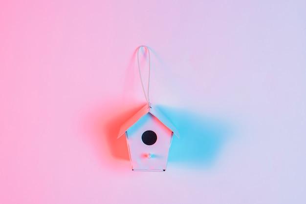 ピンクの背景に対して文字列とミニチュア巣箱の上の青い光 無料写真