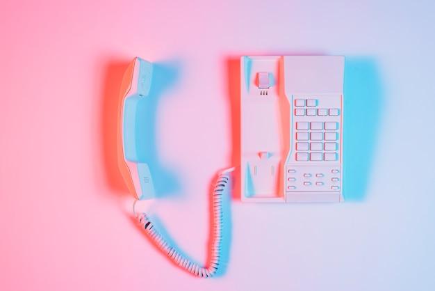 ピンクの背景に青い光の影と受信機と古い固定電話 無料写真