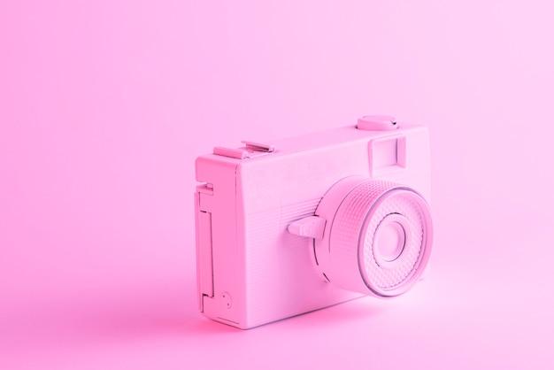 ピンクの背景に対して塗られたカメラのクローズアップ 無料写真