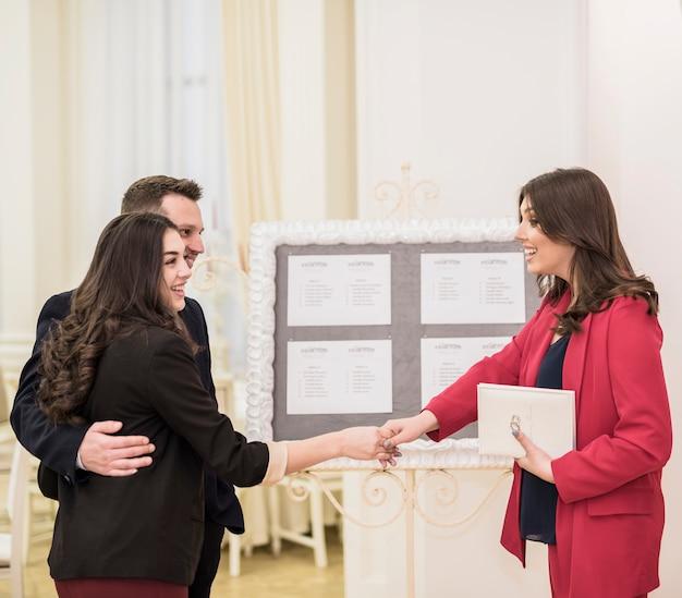 若いカップルと握手のイベントマネージャー 無料写真