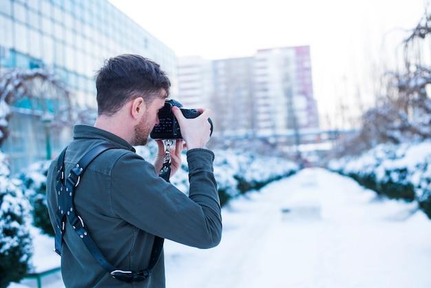 雪に覆われた通りの写真を撮る男性カメラマン 無料写真