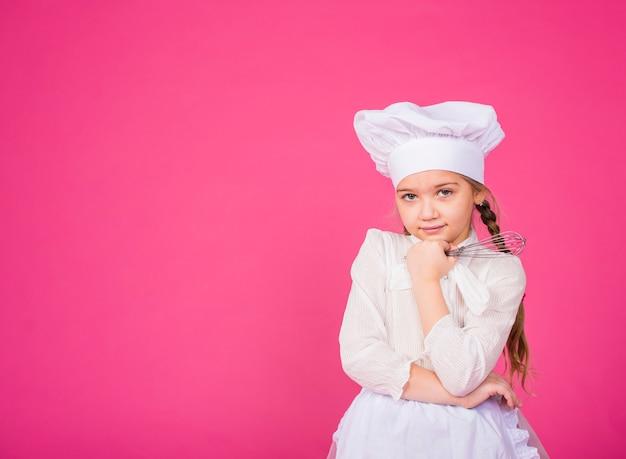 思いやりのある少女は泡立て器で料理します 無料写真