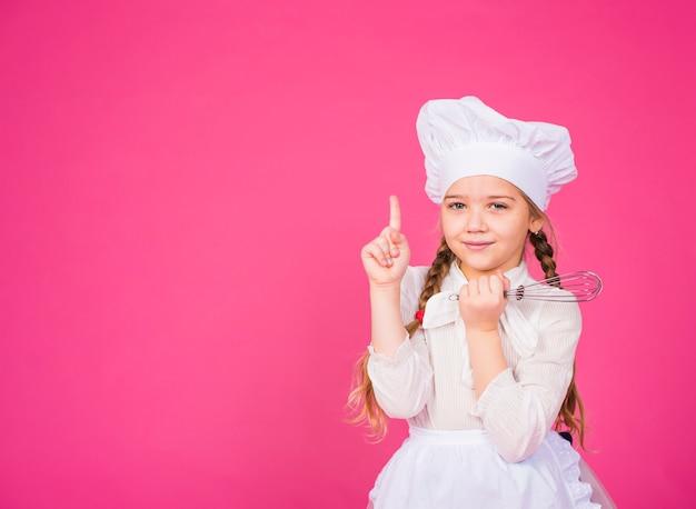 人差し指を示す泡立て器で小さな女の子料理 無料写真