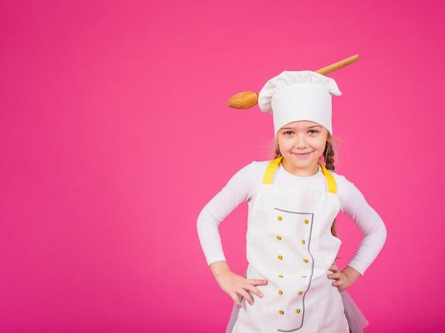 かわいい女の子料理シェフの帽子に鍋で立っています。 無料写真