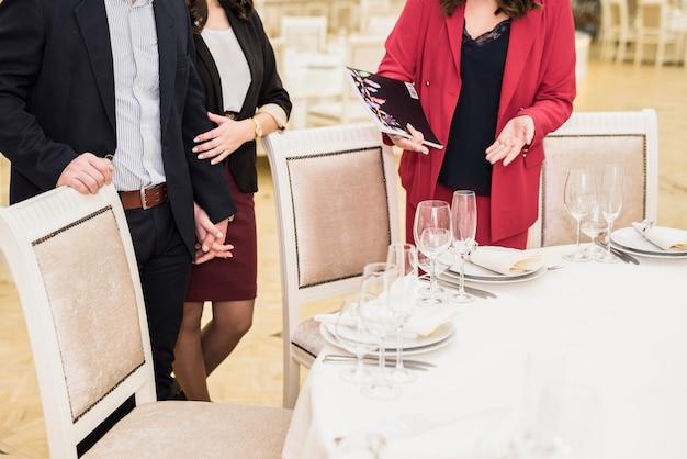 カップルに宴会場を提示するイベントマネージャー 無料写真