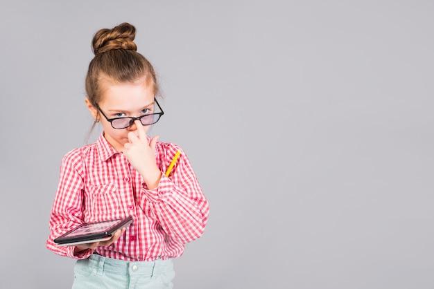 タブレットで立っているメガネでかわいい女の子 無料写真