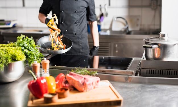 Кук подбрасывает овощи на сковороде Бесплатные Фотографии