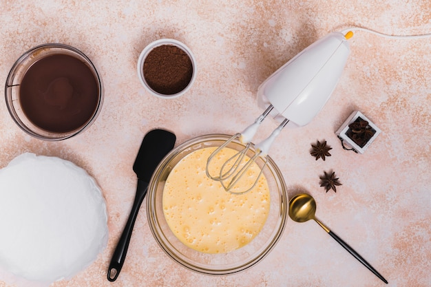 チョコレートシロップの俯瞰。ココアパウダー;アニス;へら;取鍋および織り目加工の背景に電気ミキサー 無料写真