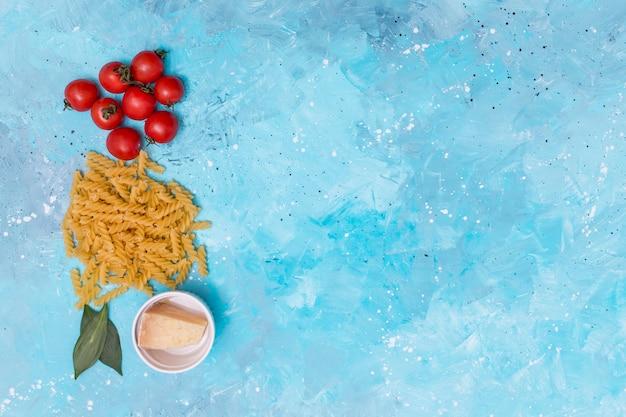 赤いトマト生のツイストフジッリパスタ。月桂樹の葉と青い背景上のチーズ 無料写真