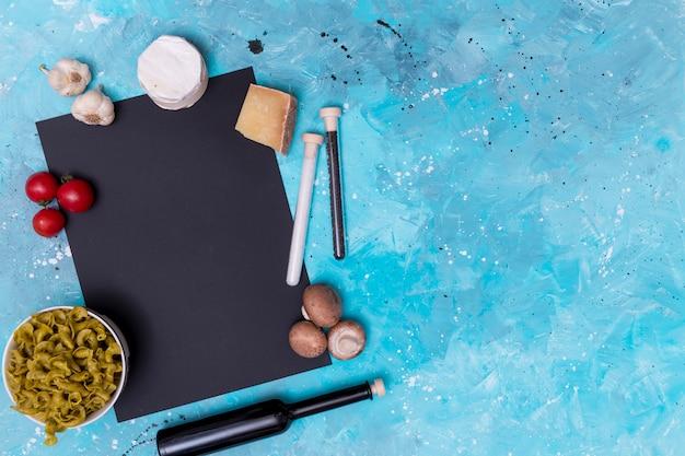 新鮮なベジタリアン食材と青い表面上の黒いスレートと未調理のパスタのオーバーヘッドビュー 無料写真