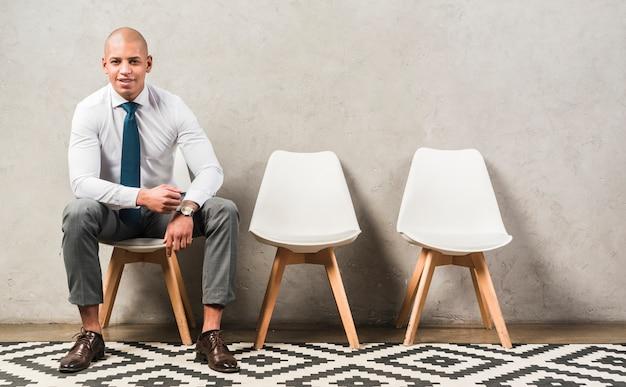 Портрет уверенно счастливого молодого бизнесмена сидя на стуле перед серой стеной Бесплатные Фотографии