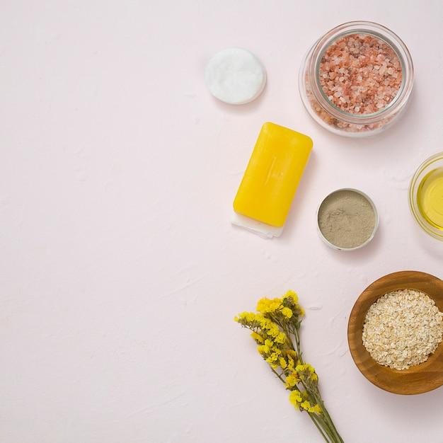 岩塩;コットンパッド。石鹸;オーツ麦;白いコンクリートの表面に黄色のリモニウムの花と化粧品製品 無料写真