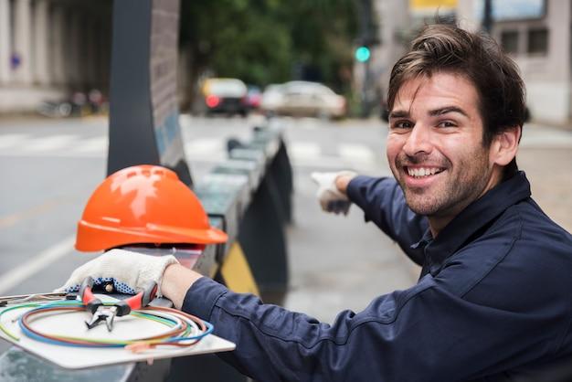 ハード帽子と路上の機器で指している笑顔の男性電気技師の肖像画 無料写真