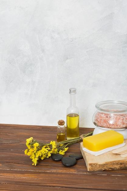 Розовая гималайская соляная банка; губка; последний; эфирное масло и лимониум цветы на столе Бесплатные Фотографии