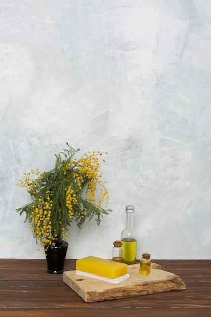 Травяное желтое мыло на сложенной салфетке и флакон с эфирным маслом рядом с желтой вазой с мимозой Бесплатные Фотографии