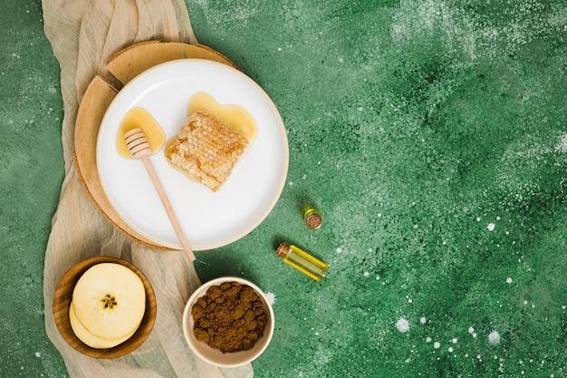 リンゴのスライスとセラミックプレート上のハニカムの俯瞰。エッセンシャルオイルとコーヒーのグリーンテクスチャ背景 無料写真