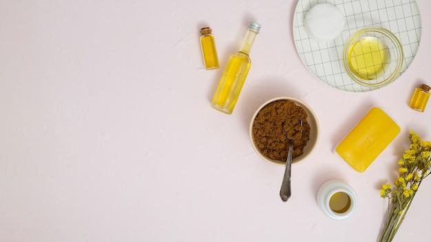コーヒー挽き器。エッセンシャルオイル;綿パッド;織り目加工の背景に黄色の石鹸とリモニウムの花 無料写真