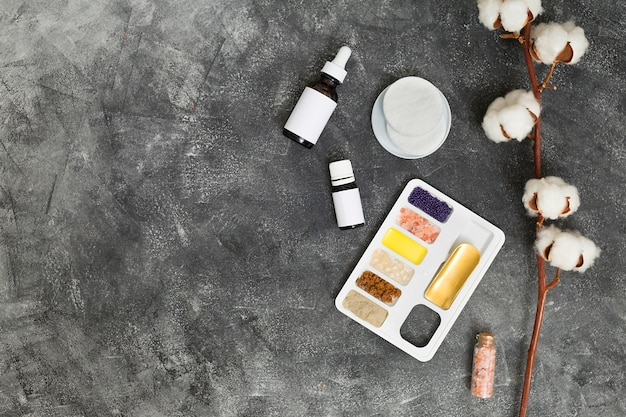 ラッスールクレイ付きホワイトトレイ。コーヒー農園;油;ロックソルトとエッセンシャルオイルのボトル、綿のパッドと黒いコンクリートの背景 無料写真