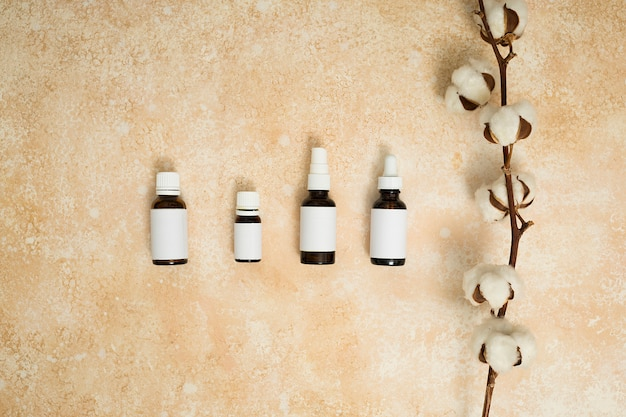 ベージュ色のテクスチャ背景のエッセンシャルオイルのボトルの種類と綿の枝 無料写真