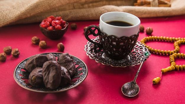 日付のフルーツとビーズのテーブルの上のコーヒーカップ 無料写真