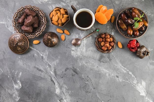 Кофейная чашка с финиками, фруктами и орехами Бесплатные Фотографии